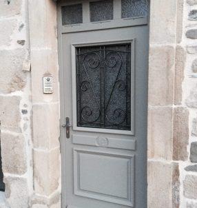 Porte d'entrée bois avec finition RAL, grille fer forgée et imposte fixe 3 carreaux.