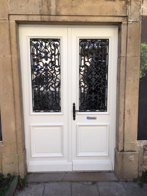 Porte d'entrée en bois finition RAL 9010 avec récupération des grilles en fer forgé.